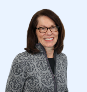Theresa Conway wearing a gray patterned jacket and black framed glasses.
